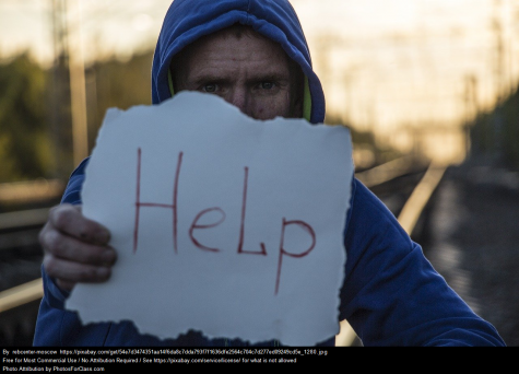 "Boy holding ""help"" sign"