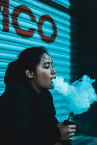 Girl vaping, releasing vapor