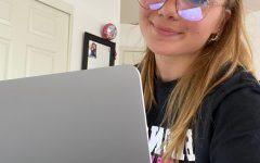 Girl sitting working on laptop.