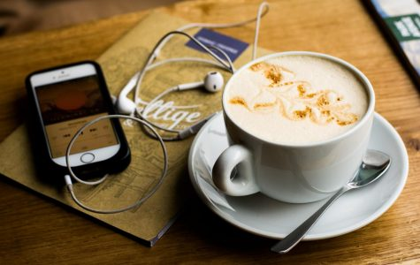 Coffee on table with iPhone and ear buds