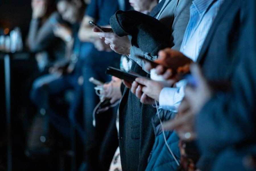Hands of multiple graduates checking phones
