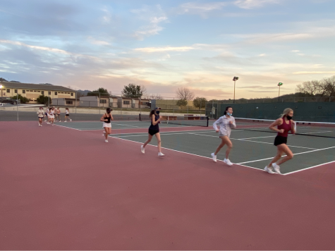 High school tennis athletes running on track