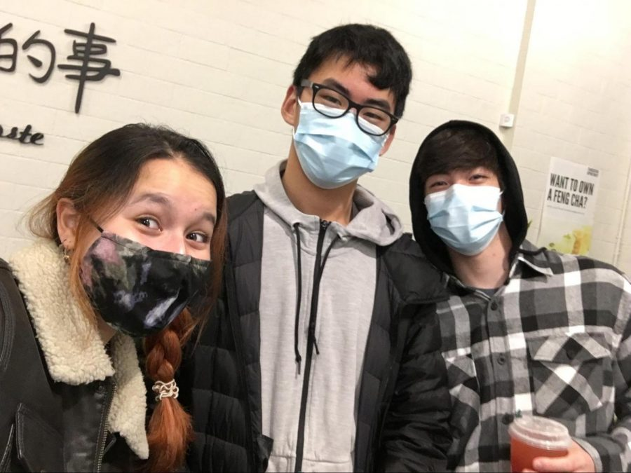 Three masked students at club meeting