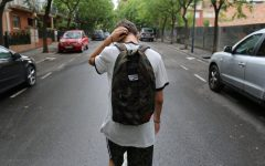 Male teen with backpack, walking away and scratching head