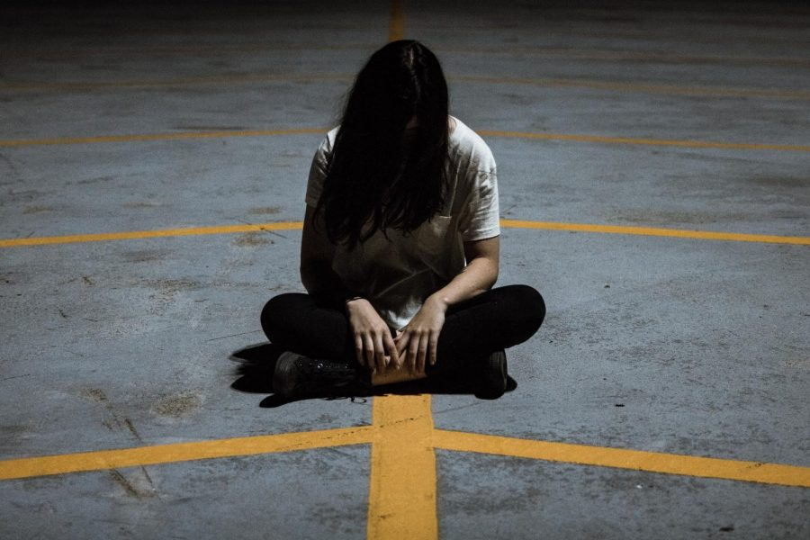 Girl sitting alone head down